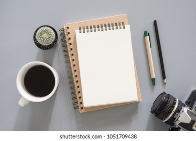 Blank notepad  with camera and coffee cup on office desk