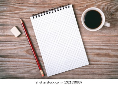 Blank notepad for copy space with coffee cup on wooden table