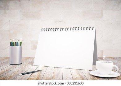 Blank notepad cover, cup of coffee and pen on wooden table, mock up