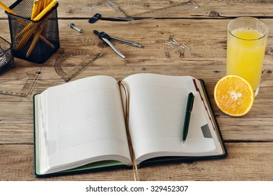 Blank notepad with a glass of fresh orange juice and office props on wooden table. Top view