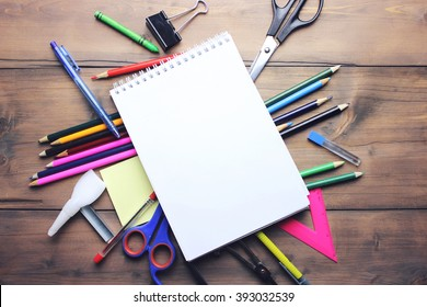 Blank notepad over school and office supplies on office table