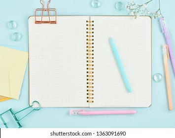 Blank notepad page in bullet journal on blue office desktop. Top view of modern bright table with notebook and flower. Mock up, copy space.