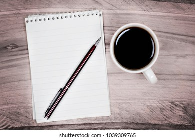 Blank notepad with pen and coffee cup on wooden table