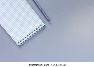 Blank notepad with pen on a grey office table. Negative space for your text and advertisement. View from above
