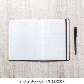 Blank notepad with pen on office wooden table.