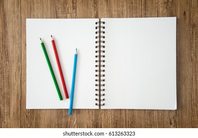 Blank notepad and pencil color on wooden blackground