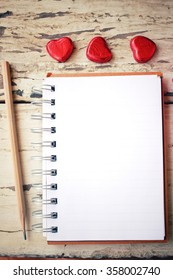Blank notepad and pencil with heart on office table