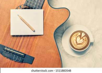 blank notepad and pencil on acoustic guitar with cup of coffee in the morning. song writing concept
