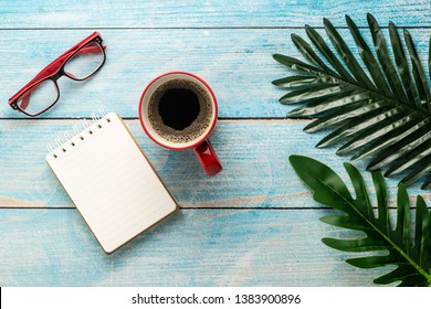 blank notepad with red cup coffee ,red glasses ,green leaf on wooden top view flat lay business relax time