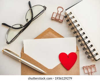 Blank notepad sheet for your congratulatory message. Close-up, view from above, wooden surface. No people. Concept of preparation for a professional holiday. Congratulations for relatives, friends and