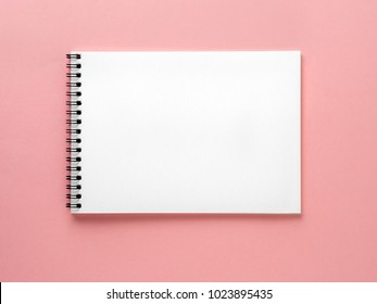 Blank notepad white page on pink desk, color background. Top view,  flat lay.