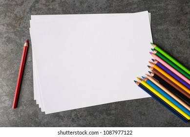 Blank office paper and multicolored pencils on dark background.