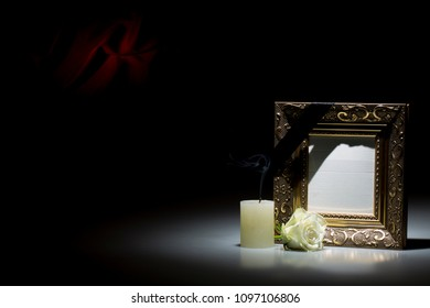 Blank old golden mourning frame, with smoky candle and white rose, on dark background with red decoration