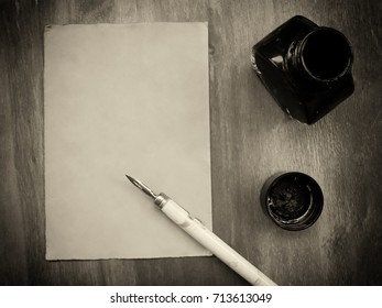 Blank old sheet of paper with a dip pen and an inkwell on a worn wooden background (view from the top or flat lay), retro style in sepia