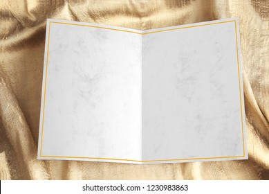 Blank open greeting card with yellow frame over gold draped fabric