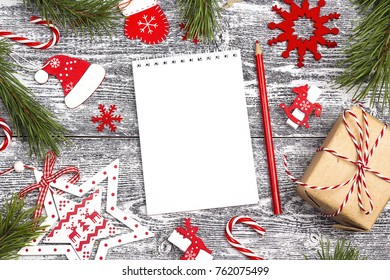 Blank open notebook with Christmas decorations and gift box. Space for text. Top view. Christmas to-do list or wish list.