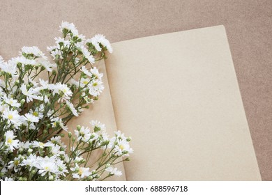 blank open notebook or diary made by craft paper with white flower bouquet on wooden background