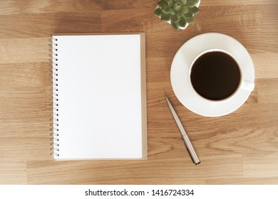 Blank open notebook next to coffee cup on wooden table with copy space that you can mock up your text for art work design.