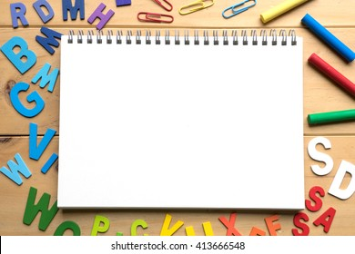 Blank open notebook with numbers and English alphabets on wooden background ready for text