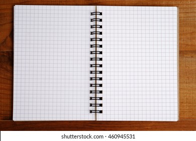 Blank open notebook on wood table background concept, top view.