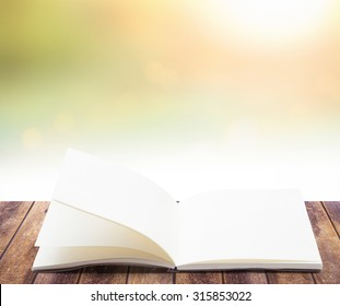 Blank opened book, diary, photo album on wooden table over blurred beautiful sunrise background.