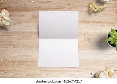 Blank opened invitation, greeting cards on wooden background to  showcase your event presentation. 3d illustration with decoration objects.