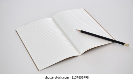 blank opened notebook paper with pencil on white background