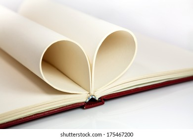 Blank opened notebook with sheets folded in form of a heart