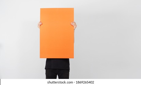 Blank orange color paper in man hand on white background.