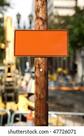 Blank orange construction sign,on wooden electric pole