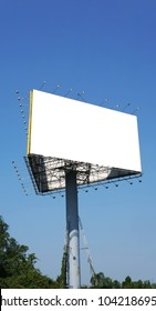 Blank outdoor billboard. Blank banner outdoor with the grass. Outdoor billboard on the blue sky.