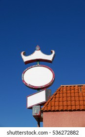 Blank oval white sign on the side of a tiled roof with a crown-like addition against blue sky