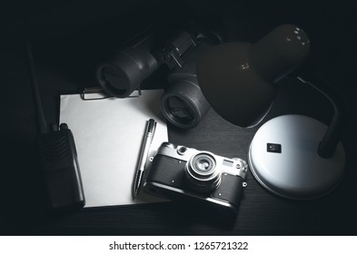 Blank page with copy space, pen, portable radio, binoculars and photo camera on a black spy agent table background. Top secret documents. Detective agent dossier. Interrogation report.