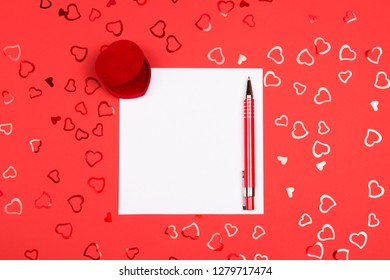Blank page of notebook with red pen for writing and wedding ring box on vibrant background decorated with heart-shaped red confetti. Valentine's Day, marriage proposal and wedding vowes concept.