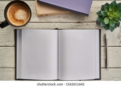 Blank page of open notebook and a cup of coffee on white wooden table desktop. Top view image.