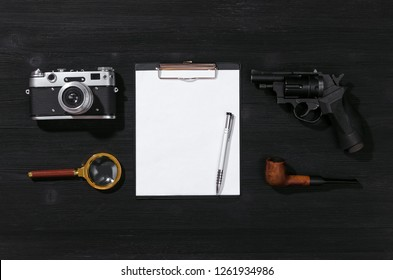 Blank page, pen, film photo camera, magnifying glass, handgun and smoking pipe on a black detective agent table background. Secret document mock up. Detective agent report. Flat lay spy table concept.