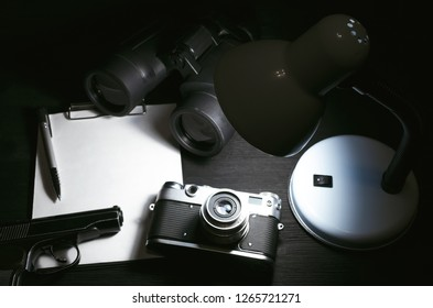 Blank page, pen, film photo camera, handgun and a binoculars on a black detective agent table background. Top view photo. Top Secret document mock up. Detective agent report.
