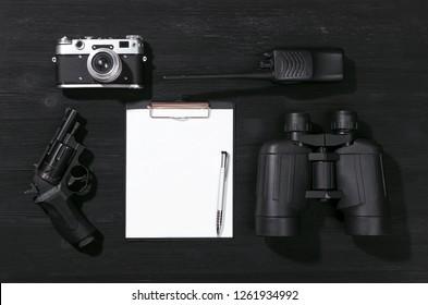 Blank page, portable radio, handgun, binoculars and photo camera on a black flatlay table background. Top secret document. Detective agent dossier. Interrogation report. Surveillance service concept.