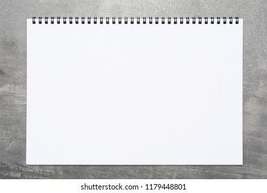 Blank page of a sketchbook over a gray surface