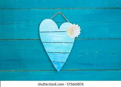 Blank pallet heart sign with spring flower hanging on antique rustic teal blue wood background; Mothers Day and Valentines Day background with painted wooden copy space