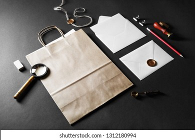 Blank paper bag, envelopes and retro stationery on black paper background.