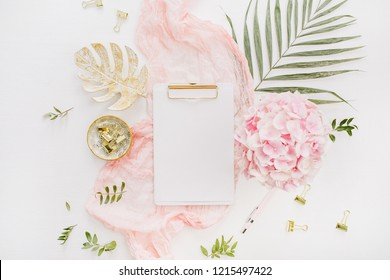 Blank paper clipboard, pink hydrangea flowers bouquet, tropical palm leaf, pastel blanket, monstera leaf plate and accessories on white background. Flat lay, top view rose gold home office desk.