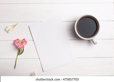 Blank paper, coffee and flower on white table, top view