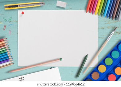 Blank Paper and Color pencil,crayons ,color pen  Watercolor paint palette on Blue Wood table with copy space.Education Back to school concept