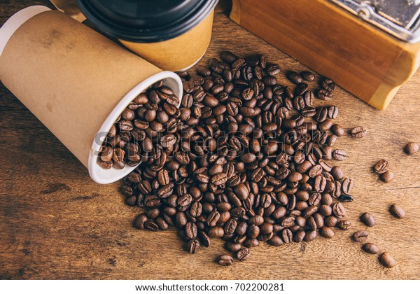 Blank paper cup with good roasted coffee beans dropped on thick wooden table