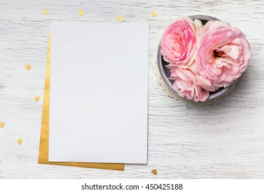 Blank paper and cute pink flowers on white wooden table, top view