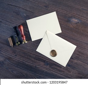Blank paper envelopes with golden wax seal, stamp, spoon and postcard on wooden background. Mockup for your design. Flat lay.