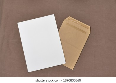 Blank paper in Kraft envelope on a brown background. Clean postcard for your signatures. Top view