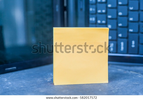 Blank paper note on wooden table over blurry laptop as a background