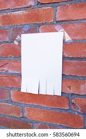 blank paper note, tear off paper, on red brick wall with copy space